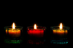 Three Lit Candles for a bottom border on black. Stock Photos