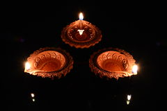 Three Clay Diyas. Three lit clay diyas lamps placed on a black background Royalty Free Stock Photo