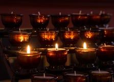 Three lit votive candles Stock Photos