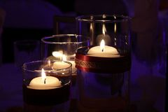 Lit candles in glass holders with purple background royalty free stock images