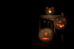 Three lit white jack o-lanterns on a bench Royalty Free Stock Photo