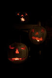 Three lit white jack o-lanterns on a bench Stock Photos