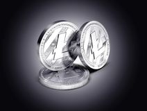 Three Litecoin physical concept coins displayed on gently lit dark background. 3D rendering. New virtual money stock illustration