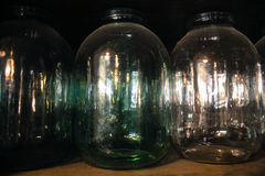 Three-liter glass bottles. Reflections on three-liter jar in the dark Royalty Free Stock Images