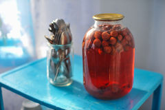 Three-liter glass jar with strawberry compote canned on blue tab Stock Images