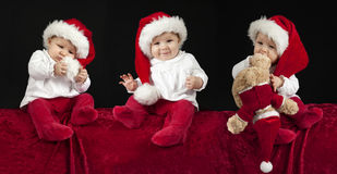 Three little babies with christmas hat Stock Images