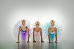 Three little ballerinas in dance studio. The silhouettes of little ballerinas in dance studio posing on a white background royalty free stock photography