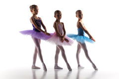 Three little ballerinas dancing in dance studio. The silhouettes of little ballerinas in dance studio posing on a white background royalty free stock photography