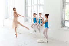 Three little ballerinas dancing with personal ballet teacher in dance studio Royalty Free Stock Photo