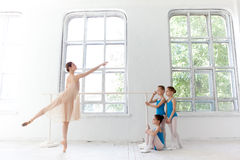 Three little ballerinas dancing with personal ballet teacher in dance studio Stock Images