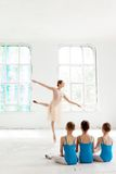 Three little ballerinas dancing with personal ballet teacher in dance studio. Three little ballerinas with personal ballet teacher in dance studio. classic stock image