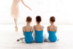 Three little ballerinas dancing with personal ballet teacher in dance studio. Three little ballerinas with personal ballet teacher in dance studio. classic stock images
