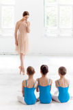 Three little ballerinas dancing with personal ballet teacher in dance studio. Three little ballerinas with personal ballet teacher in dance studio. classic royalty free stock photography