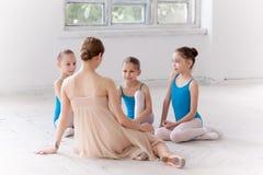 Three little ballerinas dancing with personal ballet teacher in dance studio Stock Photo
