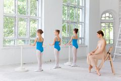 Three little ballerinas dancing with personal ballet teacher in dance studio. Three little ballerinas with personal classic ballet teacher in dance studio posing royalty free stock images