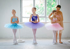 Three little ballerinas with personal ballet teacher in dance studio. On a white background Stock Photos