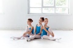 Three little ballet girls sitting and posing together Stock Images