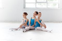 Three little ballet girls sitting and posing together Royalty Free Stock Photos