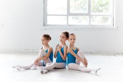 Three little ballet girls sitting and posing together Royalty Free Stock Image