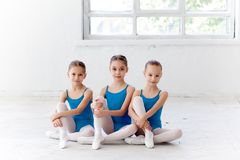 Three little ballet girls sitting and posing together Royalty Free Stock Photo