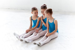 Three little ballet girls sitting and talking together Stock Photos