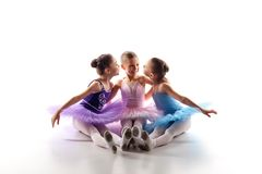 Three little ballet girls sitting in tutu and posing together Stock Photos