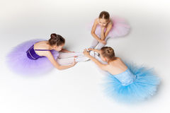 Three little ballet girls sitting in tutu and posing together Royalty Free Stock Photos