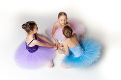 Three little ballet girls sitting in tutu and posing together Stock Photo