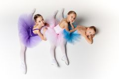 Three little ballet girls sitting in tutu and posing together Stock Images