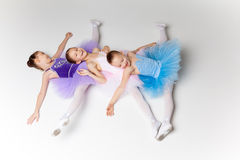 Three little ballet girls in tutu lying and posing together Stock Photos