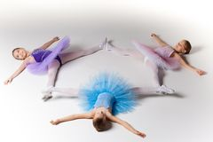 Three little ballet girls in tutu lying and posing together Royalty Free Stock Image
