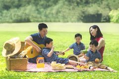 Three little boys picnicking with their parents. Three cute little boys enjoying their holiday while picnicking with their parents in the park Stock Photography