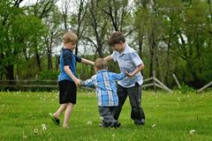 Three boys holding hands ring around the Rosie. Three little boys running in a circle, playing and holding hands. Rural setting royalty free stock photos