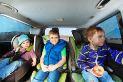 Three little boys sitting in safety car seats Royalty Free Stock Images