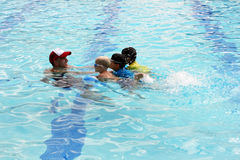 Three little boys with swim instructor. Male swim instructor pulling three little boys in the water to practice kicking Royalty Free Stock Photos