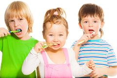 Three little brushing their teeth Stock Photo