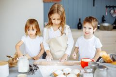 Three little chefs enjoying in the kitchen making big mess. Kids making cookies in the kitchen royalty free stock image