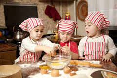 Three little chefs in the kitchen. Three little chefs enjoying in the kitchen making big mess. Little girls making bread in the kitchen Royalty Free Stock Images