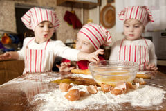 Three little chefs in the kitchen. Three little chefs enjoying in the kitchen making big mess. Little girls making bread in the kitchen Stock Photography
