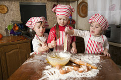Three little chefs in the kitchen. Three little chefs enjoying in the kitchen making big mess. Little girls making bread in the kitchen Royalty Free Stock Image