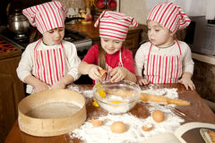 Three little chefs in the kitchen. Three little chefs enjoying in the kitchen making big mess. Little girls making bread in the kitchen Stock Photo