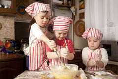Three little chefs in the kitchen. Three little chefs enjoying in the kitchen making big mess. Little girls making bread in the kitchen Stock Photos