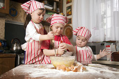 Three little chefs in the kitchen. Three little chefs enjoying in the kitchen making big mess. Little girls making bread in the kitchen Royalty Free Stock Photos