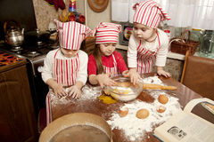 Three little chefs in the kitchen Stock Image