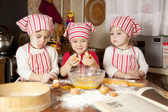 Three little chefsin the kitchen. Three little chefs enjoying in the kitchen making big mess. Little girls making bread in the kitchen Stock Images
