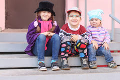 Three little children in bright clothes sitting on stairs Stock Photography