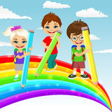 Three little children drawing together a beautiful colorful rainbow with color pencils Royalty Free Stock Photos