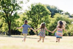 Three little children running on a green field royalty free stock photo