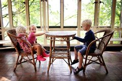 Three Little Children Sitting at an Old Bistro Table in a Sunroom Waiting for Food. Three little children are sitting at an old wicker bistro table in a sun room stock photography