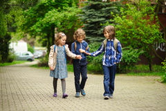 Three little friends go to school. Stock Photos